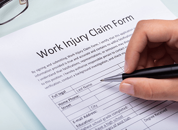 hand holding a pen to fill out a work injury claim form