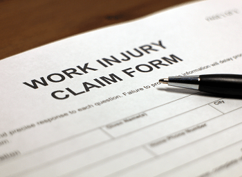 Work injury claim form with a pen on top